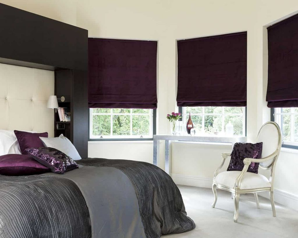 Purple roman blinds cardiff in a bedroom behind the bed and a dresser
