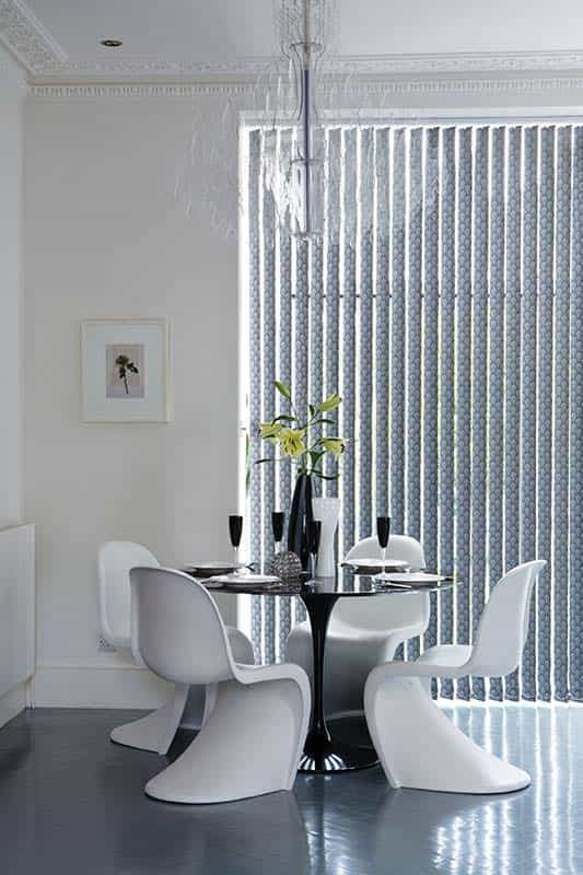 White Vertical blinds Cardiff in a white room behind a table and chairs