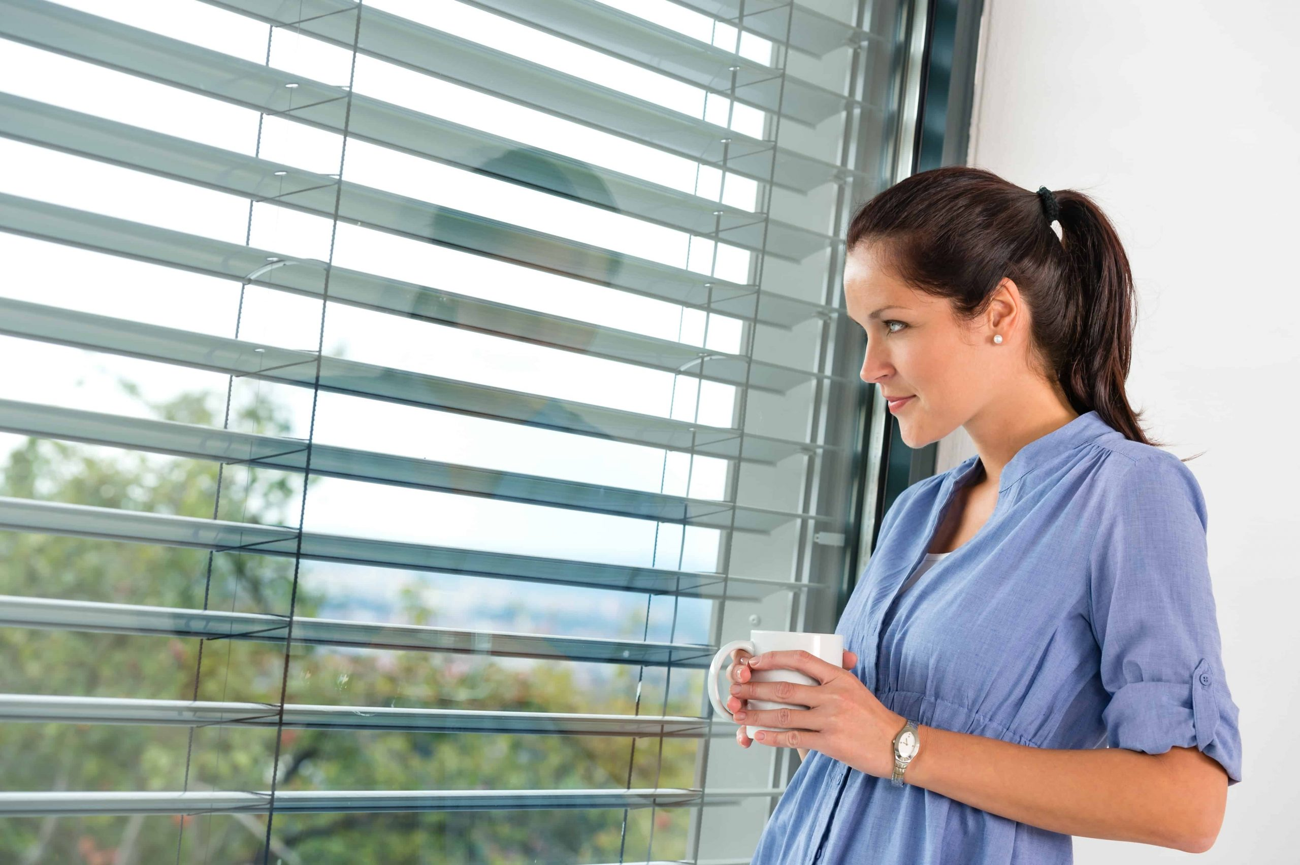 Young woman day dreaming looking window blinds Cardiff drinking tea
