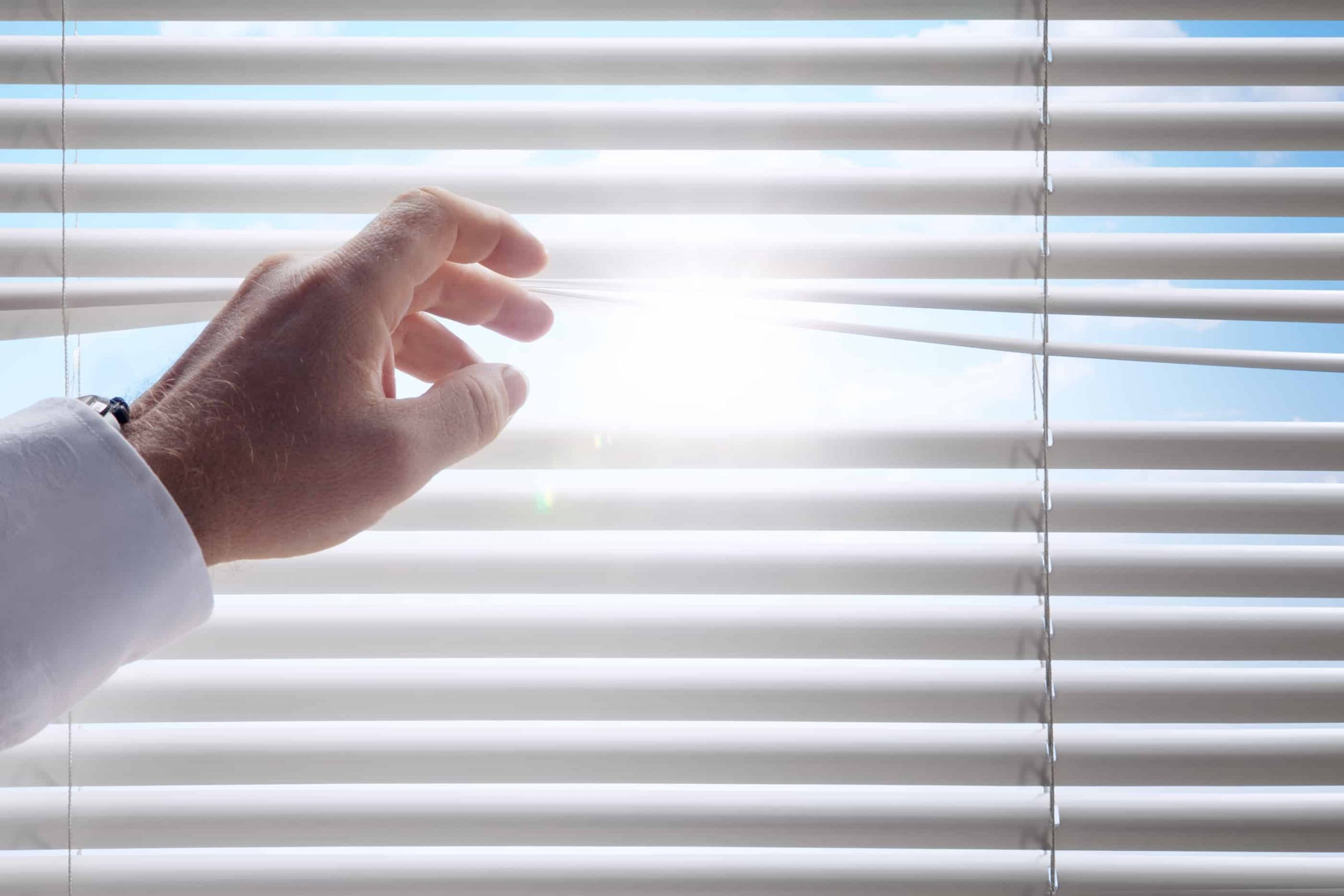 A man opening up some blinds with the sun shining through
